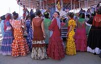 Sanlucar de Barrameda, a group of women in flamenco dress watching a merry go round