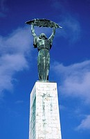 Budapest, woman holding up a palm leaf, the Liberation Monument on Gellert Hill
