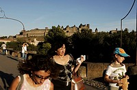 Carcassonne, tourist passing over the roman bridge over the Aude river outside the walls of the medieval city