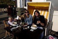Sylt, a young family in a beach chair at the terrace of a restaurant