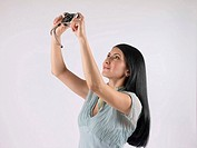 Woman holding up camera to take pictures (thumbnail)
