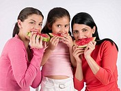 Two women and a child eating water melon