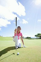 Woman playing golf, smiling
