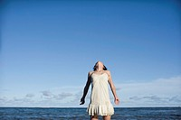 Woman standing in sea, looking into sky