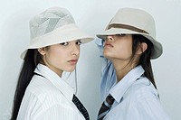 Two young female friends dressed in button down shirts, ties and hats, looking at camera, portrait