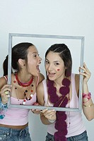 Two young female friends holding up picture frame, one yelling into the other's ear, portrait