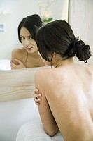 Young woman looking into bathroom mirror