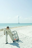 Man in suit pulling garbage can across sunny beach, looking back over shoulder, full length