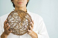 Man holding up wicker sphere, cropped view