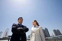 Businessman and businesswoman standing in center of city