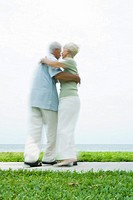 Senior couple dancing on sidewalk overlooking ocean, full length, blurred motion
