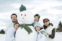 Group of young friends gathered around snowman