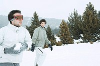Young male friends in the snow, one holding a snowball