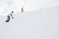 Snowboarder descending slope, low angle view