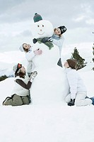 Young female friends grouped around snowman