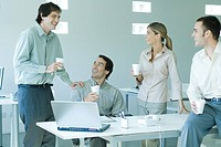 Business associates gathered around table, holding disposable cups, laughing
