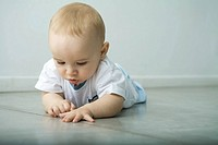 Baby lying on floor, looking at seam in flooring