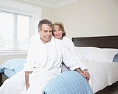 Mature couple wearing bathrobes, sitting on bed, portrait