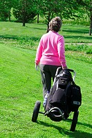 A woman golfer pulls a golf bag on a golf course  Finland