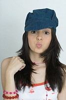 Teenage girl looking at camera, puckering lips, wearing cap, portrait
