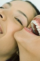 Cropped view of two young friends laughing together, one looking at camera, extreme close-up