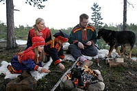 A Sami family dressed in the traditional Lapp dress and a Lapland reindeer dog are having a picnic by open fire in Inari, Finnish Lapland  Finland