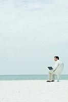 Businessman sitting in chair on beach, using laptop computer, looking away