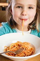 Small girl eating spaghetti with tomato sauce