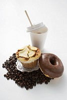Muffin, doughnut, coffee beans and a plastic cup of coffee