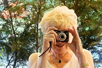 glamorous, 70 year old lady taking a photo of the photographer, smiling