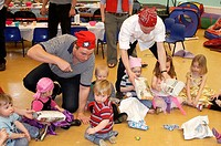 group of chidren playing pass the parcel, at a childrens pirate party, with the dads supervising