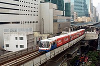 Skytrain leaving Sala Daeng Station with Silom Buildings at the Background, Bangkok. Thailand