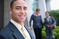 Young business man, two women in background