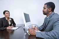 Mature business man and woman sitting at desk, having meeting in office