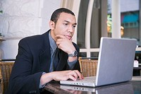 Young businessman sitting at table using laptop