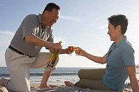Mature couple drinking cognac on beach, side view