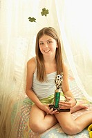 Girl 10-11 sitting on bed and holding soccer trophy, smiling, portrait