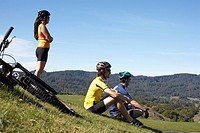 Two men and woman on bike trip in landscape, resting on hillside, side view