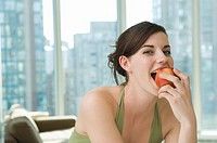 Woman eating apple, portrait