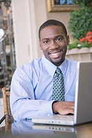 Young businessman using laptop, smiling, portrait