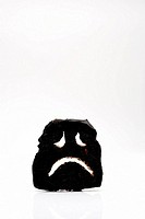 Sad face made of burnt toast on a white background