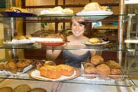 Young woman behind display case in bakery