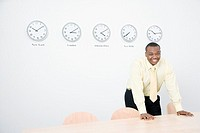Business man standing in office in front of clocks on wall