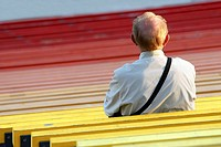 An old man at stadium bench