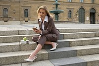 businesswoman, sit, stone stairway, lunchbox, apple, water bottle, iPod,