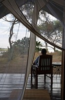 Young Man on the Porch Enjoying the View of the Zambezi River  Southern Province, Zambia