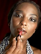 Close-up of a Woman Putting on Lipstick  Studio Shot