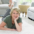 Happy woman lying down on living room carpet
