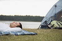 Man napping beside a tent