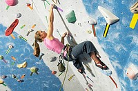Woman reaching for hand hold on climbing wall